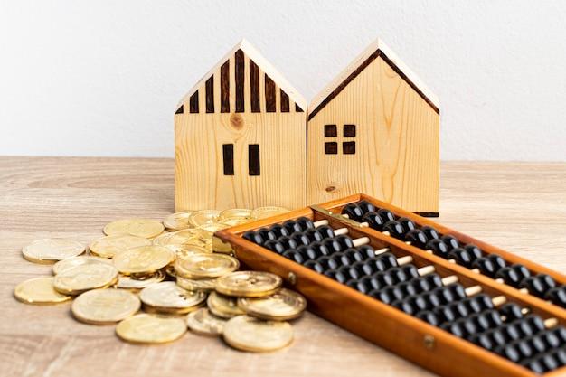 麻袋の金貨とコピースペースのあるテーブルにそろばんが付いた2軒の家