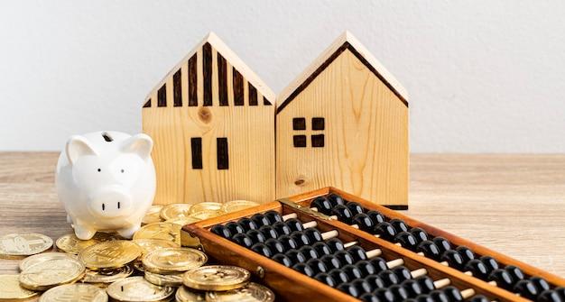 麻袋ピンキーバンクの金貨とコピースペースのあるテーブルに中国のそろばんが付いた2軒の家
