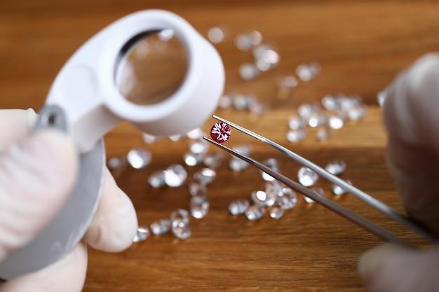 白い手袋のゴルトシットはピンクのピンセットを保持します