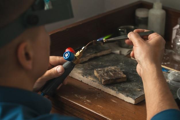 휘발유 버너로 금 요소를 녹이는 goldsmith. 직장에서 보석입니다. 전문 도구를 사용하여 공예 보석을 만들기 위한 데스크탑입니다.