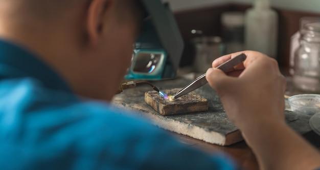 휘발유 버너로 금 요소를 녹이는 goldsmith. 머리 돋보기를 가진 보석상. 전문 도구를 사용하여 공예 보석을 만들기 위한 데스크탑입니다.