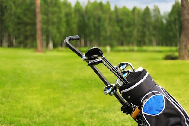 Сумка для гольфа и клюшки напротив сосредоточенного зеленого с песчаными ловушками
