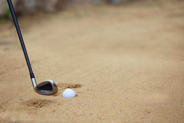 ゴルフコースのサンドバンカーのゴルフボールとクラブ