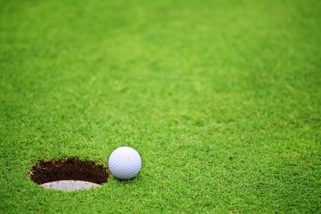 ゴルフコースのグリーンのカップのリップの穴の近くのゴルフボール