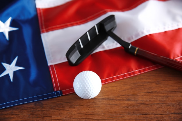 나무 테이블에 골프 공, 클럽 및 미국 국기. 인기 있는 스포츠 개념