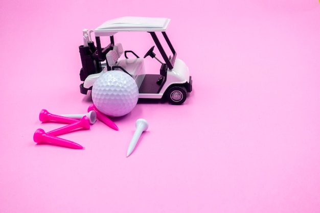Golf ball and golf cart are on pink with tees