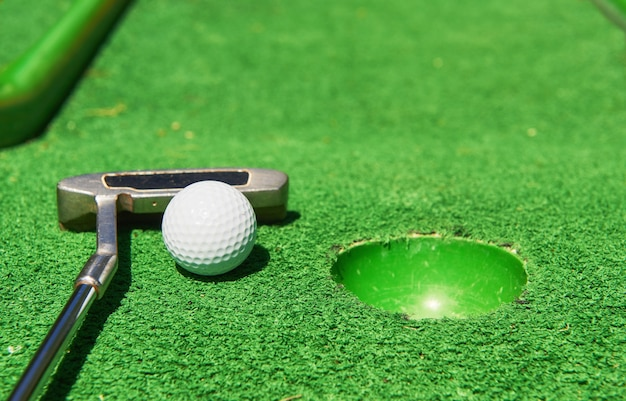 Golf ball and golf club on artificial grass.