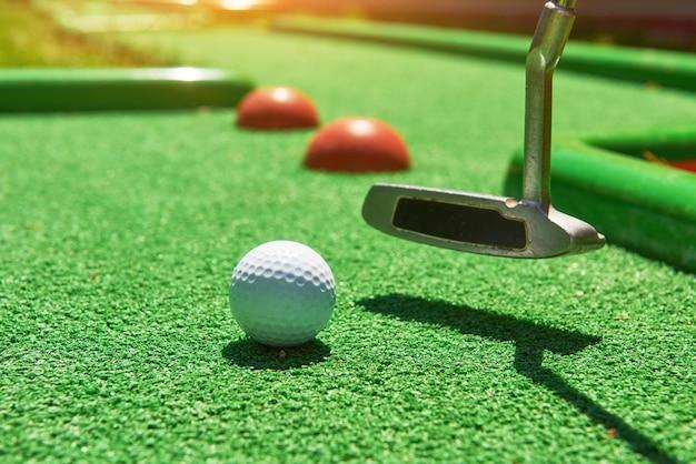 Golf ball and golf club on artificial grass.