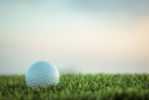 Golf ball on grass on sky background