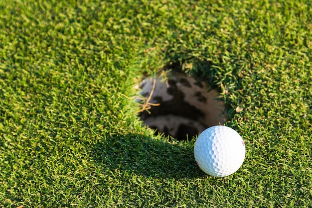 Golf ball on green over a blurred hole