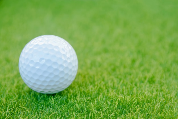 Golf ball on green grass ready to play at golf course.