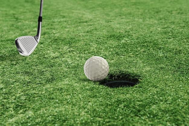 녹색 잔디 필드에 구멍 근처 골프 공
