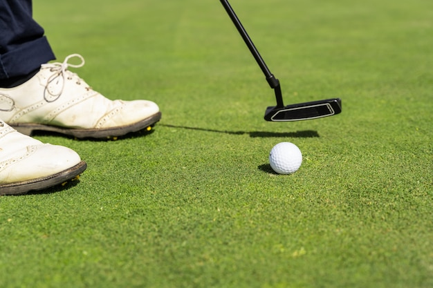 Golf ball and a person's shoes on a golf course