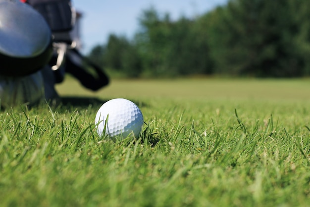 Golf ball and pin are ready to play, placed in a green lawn with a natural background.