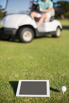 Golf ball on tee by digital tablet