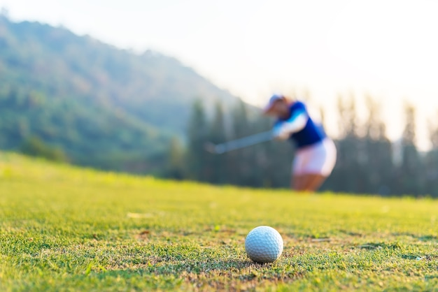 Golf ball and tee on green grass background