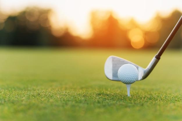 Golf ball on tee playing sports on green fairway.
