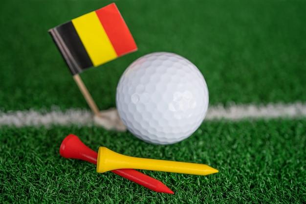 緑の芝生や芝生にドイツ国旗とティーが付いたゴルフボールは、世界で最も人気のあるスポーツです。
