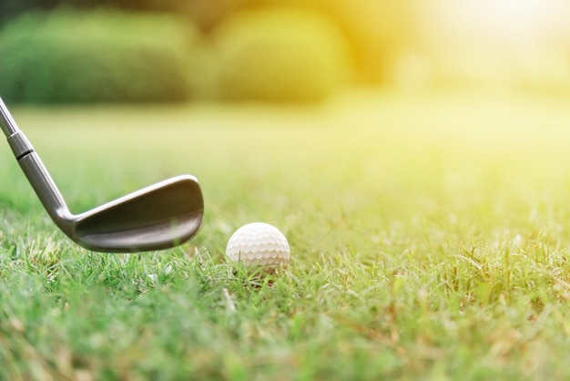 Golf ball with golf club on green grasses with sunlight.