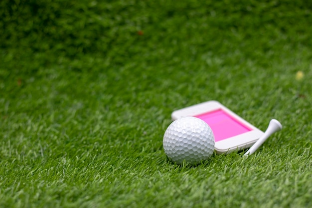 Golf ball with mobile phone on green grass.
