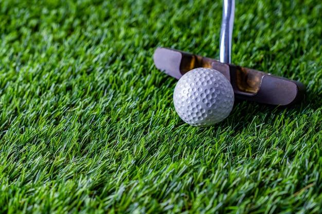 푸른 잔디에 퍼 터와 골프 공