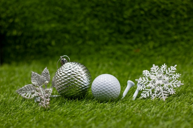 Golf ball with snow flake and christmas ornament are on green grass