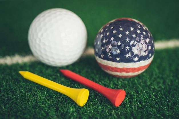 世界で最も人気のあるスポーツである緑の芝生や芝生にアメリカ国旗とティーが付いたゴルフボール。