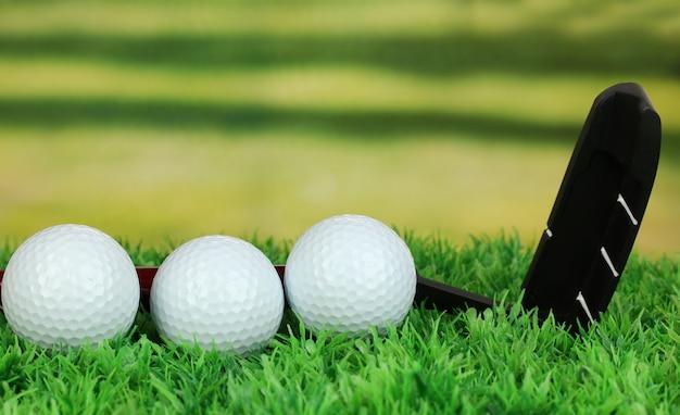 Мячи для гольфа и водитель на зеленой траве на открытом воздухе крупным планом