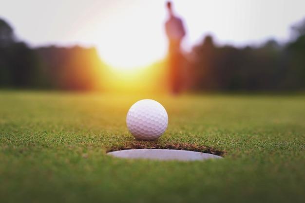 Мячи для гольфа и гольф-клуб на зеленой траве блестящим светом солнца