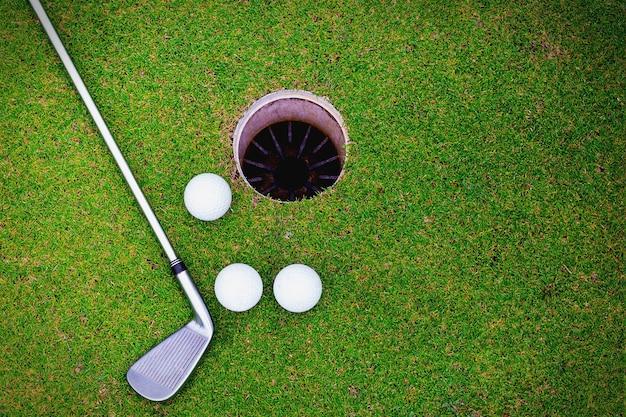 Мячи для гольфа и гольф-клуб на зеленой траве