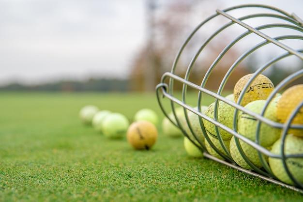 Мячи для гольфа и палки на зеленом поле для гольфа