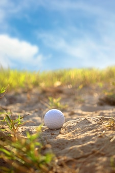 Golf balls on the sand on the field and sky.