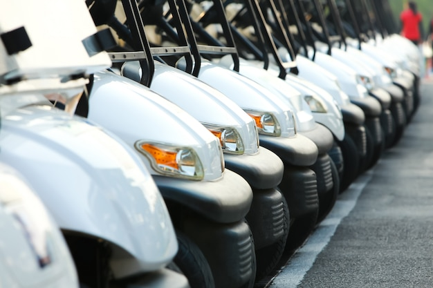 Golf cars or golf carts in a row outdoors on a sunny spring day
