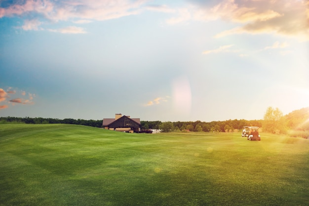 Golf cars on trimmed lawn, game course at sunset