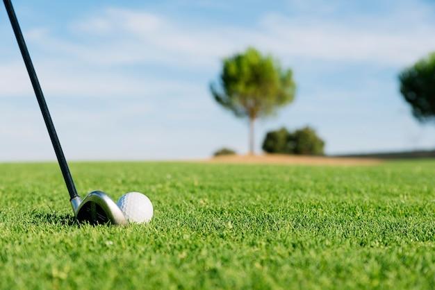 Гольф-клуб и мяч в траве. концепция гольфа.