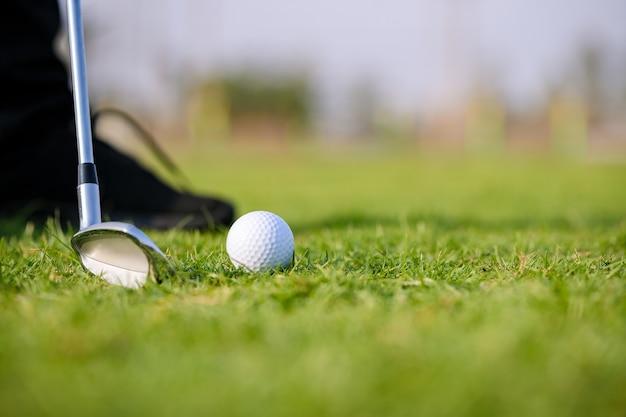 朝の美しいゴルフコースの緑の芝生の上のゴルフクラブとゴルフボール。緊張を和らげ、脳機能を刺激するスポーツ。