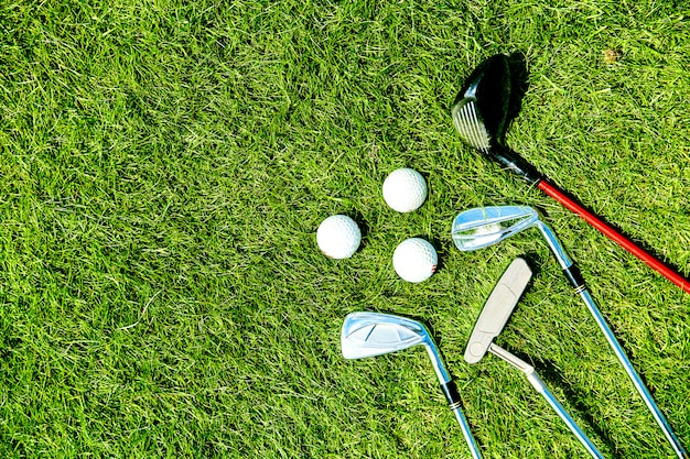 Golf clubs and balls on grass background for text