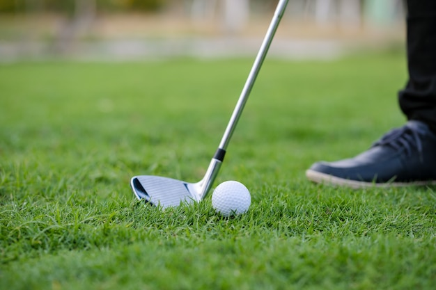 Golf clubs and golf balls on a green lawn in a beautiful golf course with morning