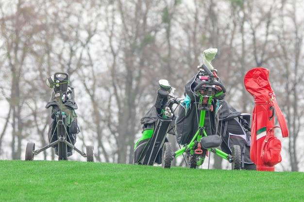 Набор клюшек для гольфа на тележке, готовой для игры в гольф. поле для гольфа на зеленой лужайке.