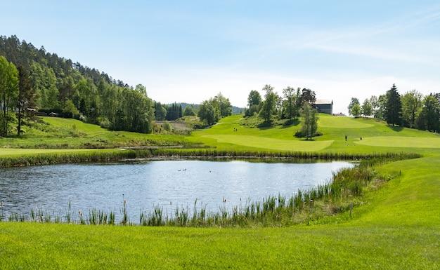 Поле для гольфа с прудом, голубым небом и зеленой природой