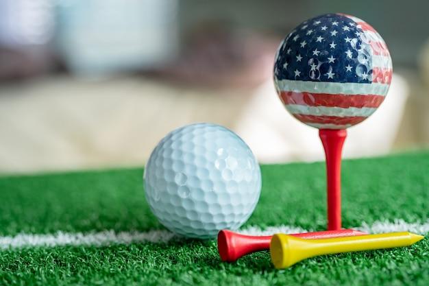 世界で最も人気のあるスポーツである緑の芝生またはフィールドに米国旗が付いたゴルフグローブワールドボール。 Premium写真