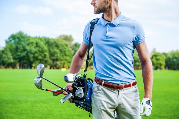 ゴルフは生き方です。緑の芝生を歩きながらドライバーとゴルフバッグを運ぶ男性ゴルファーのトリミング画像