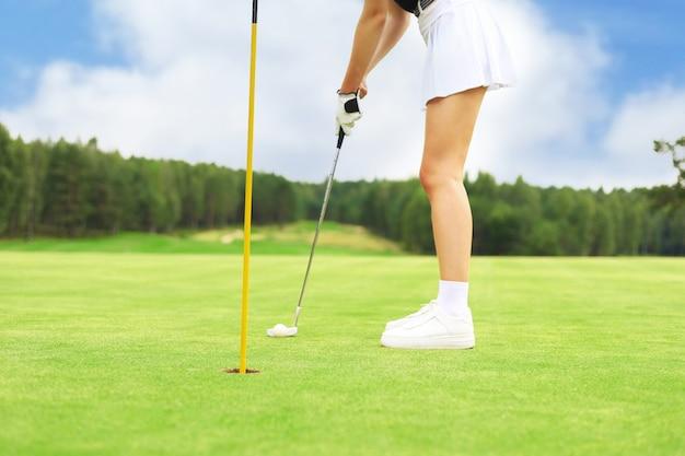グリーン打球を穴に入れるゴルフプレーヤー。