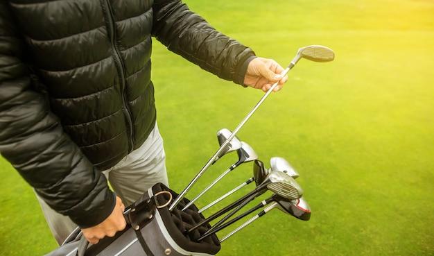 그의 경기 경쟁을 위해 클럽을 선택하는 골프 선수