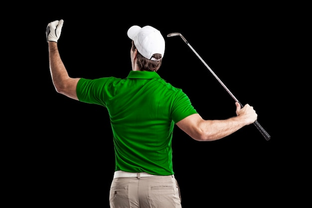 Golf player in a green shirt celebrating, on a black background.