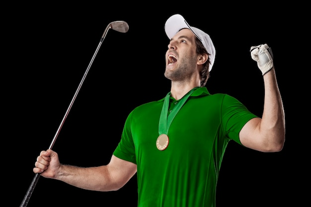 Golf player in a green shirt celebrating with a golden medal, on a black background.