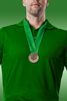 Golf player in a green shirt celebrating with a golden medal, on a green background.