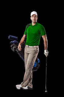 Golf player in a green shirt, standing with a bag of golf clubs on his back, on a black background.