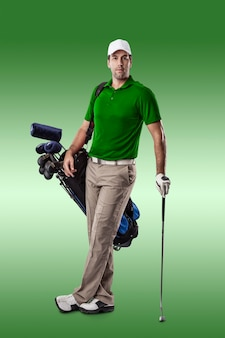 Golf player in a green shirt, standing with a bag of golf clubs on his back, on a green background.