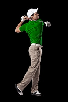 Golf player in a green shirt taking a swing, on a black background.